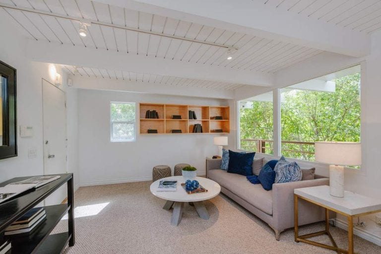 The gray carpeted flooring of this living room blends with the gray cushioned sofa below the large glass windows. This brightens the white walls with natural lights. This also does the same for the white shiplap ceiling with exposed wooden beams.