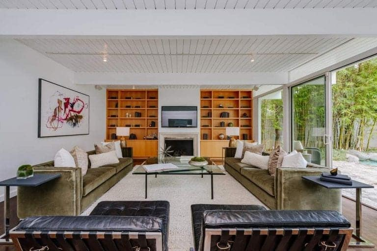 This large and bright formal living room has a Beach-style vibe to its white shiplap plank ceiling and its white exposed wooden beams. This is complemented by the two large wooden shelves on the far wall flanking the fireplace and the TV.