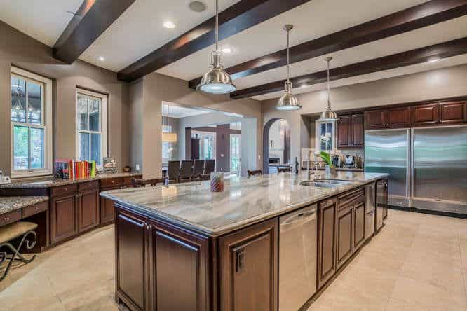 This bright and spacious kitchen has a beautiful ceiling that is adorned with stainless steel pendant lights and dark wooden exposed beams that match the tone of the shaker cabinets and drawers of the large kitchen island and the peninsula.