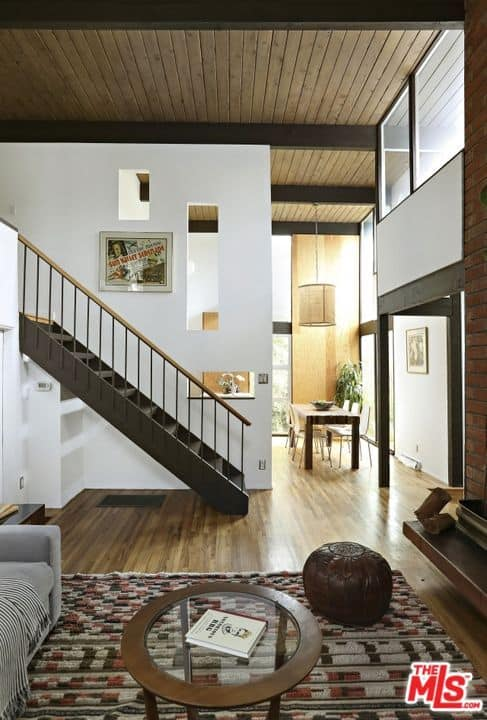 This is a great hall that houses the living room and the dining area on the far corner by the tall glass walls. These are on the same hardwood flooring and under the same high wooden ceiling with exposed wooden beams that contrast the tall white wall in the middle.