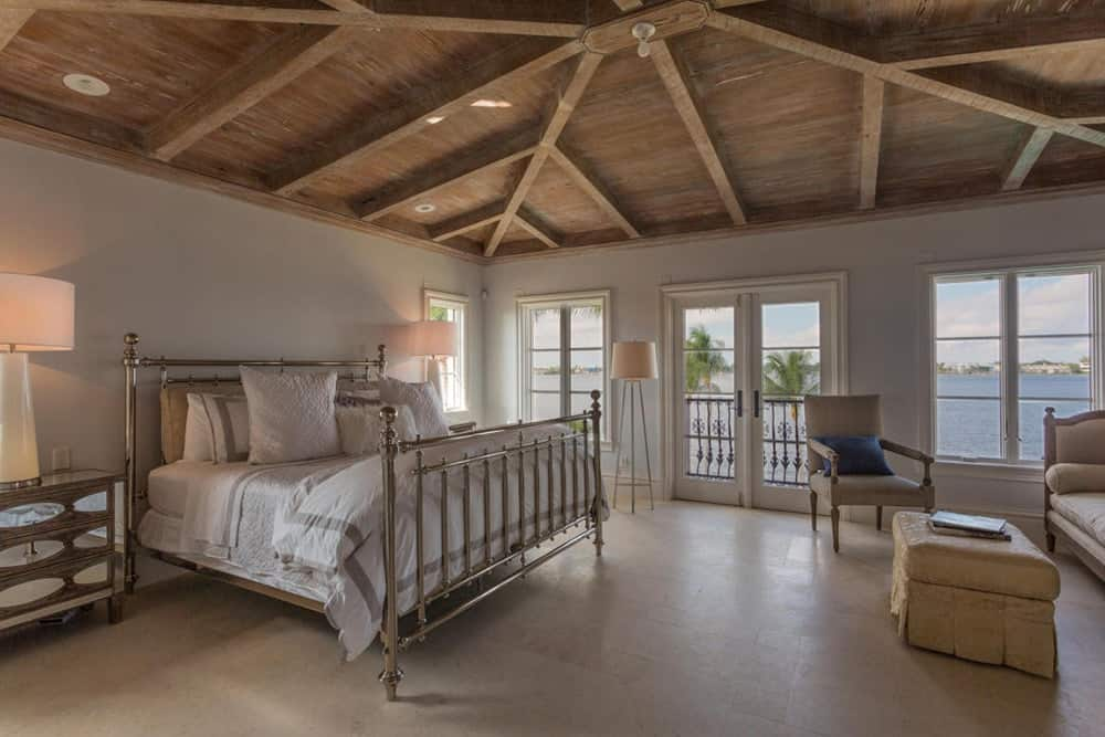 This is a charming and cozy primary bedroom with metal railings on its four-poster bed topped with a comfortable white cushion and pillows. There is also a peaceful sitting area at the other side of the room that is elevated by its consistent wooden ceiling and its exposed wooden beams.