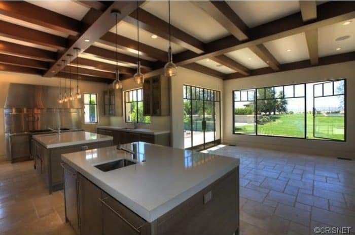 This is a large kitchen with a wide beige marble flooring that has enough space for two kitchen islands that is both topped with warm pendant lights hanging from the large exposed wooden beams of the ceiling. This is augmented by the brilliant glass windows and doors.