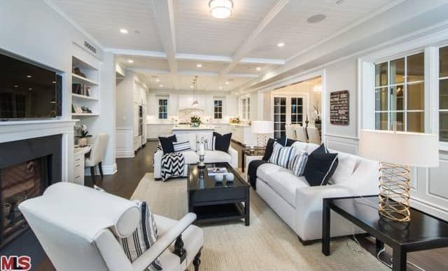The white shiplap ceiling and its matching white beams are brightened by the various recessed lights and the flush-mount ceiling lighting over the living room area that has a bright white cushioned sofa set contrasted by the black wooden coffee table.