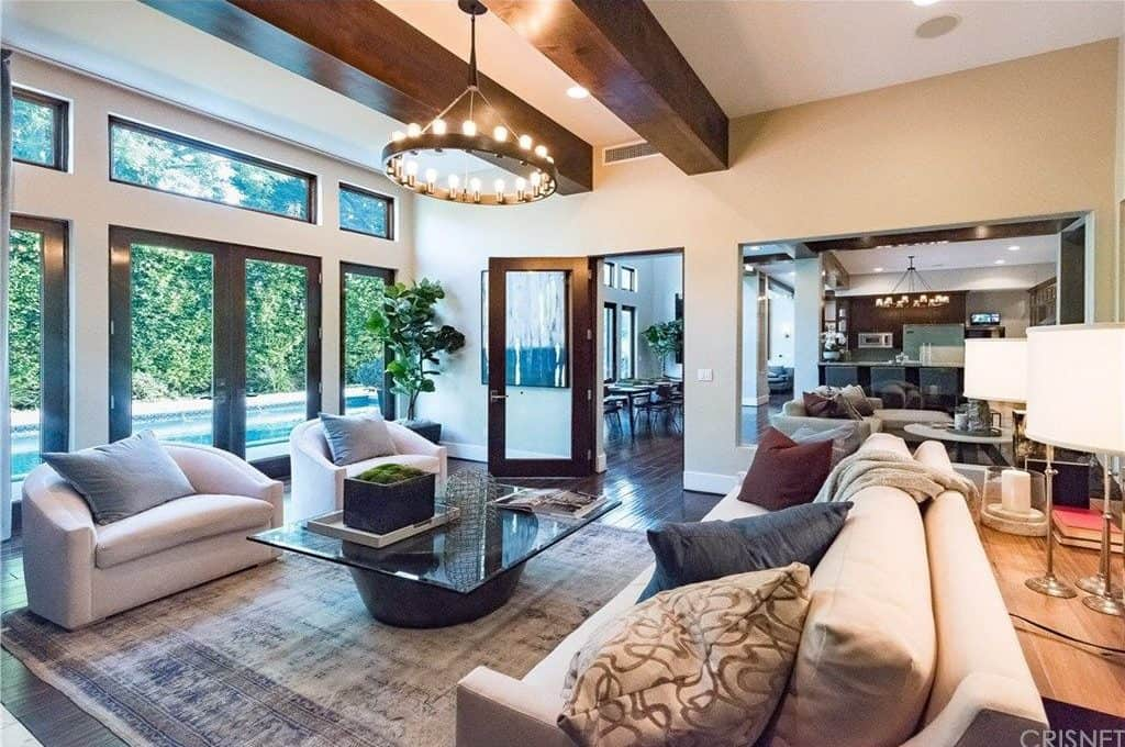 The bright round chandelier that hangs in between the two large beams of the ceiling is casting out warm yellow lights that goes well with the light hue of the cushioned sofa set that surrounds the large glass-top coffee table over the distressed area rug.