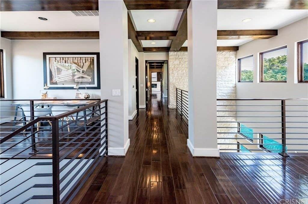 This is the second floor hallway of this home. It has a dark hardwood flooring that is contrasted by the flanking light gray columns that also contrast the dark wooden beams of the ceiling. This is augmented by the bordering dark iron railings.