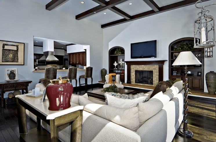 The high white ceiling of this large living room is dominated by the contrasting checkered pattern of the wooden beams. This is matched with the hues of the fireplace mantle and the hardwood flooring that contrasts the L-shaped sectional sofa.
