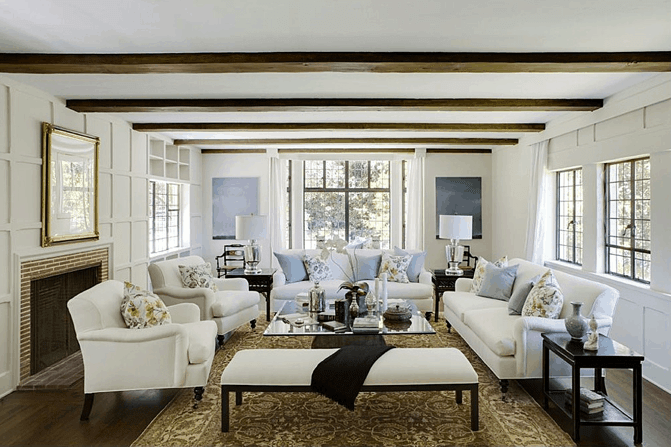 The centerpiece of this bright living room is the glass-top square coffee table that is surrounded by the white cushioned sofa set and a bench. These are all under the white ceiling that is contrasted by its exposed wooden beams that match the hardwood flooring.