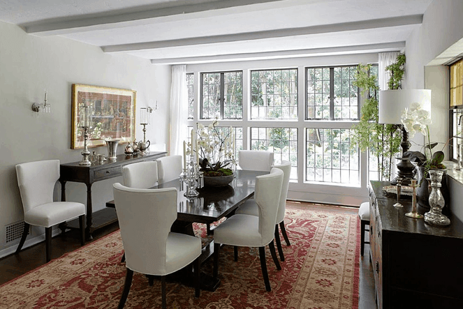 The white cushioned wing-backed chairs stand out against the red patterned area rug underneath and the sleek black rectangular dining table. This setup is brightened by the wall of glass windows that bring natural lights to the white ceiling and its beams casting shadow.