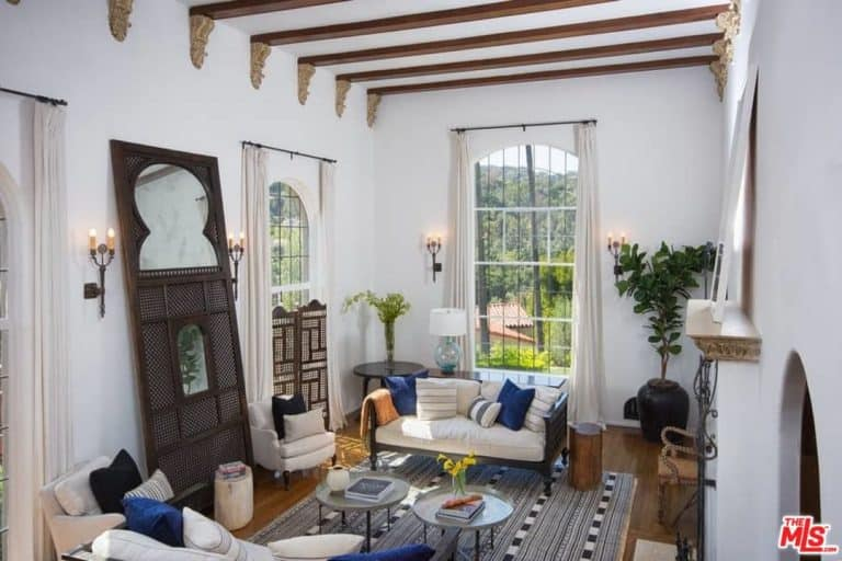 The high white ceiling has exposed wooden beams that are adorned with decors on its ends that stand out against the white wall. These walls are also adorned with the dark brown wall lamps, potted plant at the corner and two large arched windows.