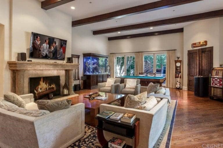 This is a great room gives a large space for the living room and the gaming area at the far end both under the same high ceiling with exposed wooden beams and recessed lights. The white walls of this great room is dominated by the large fireplace and the large fish tank.