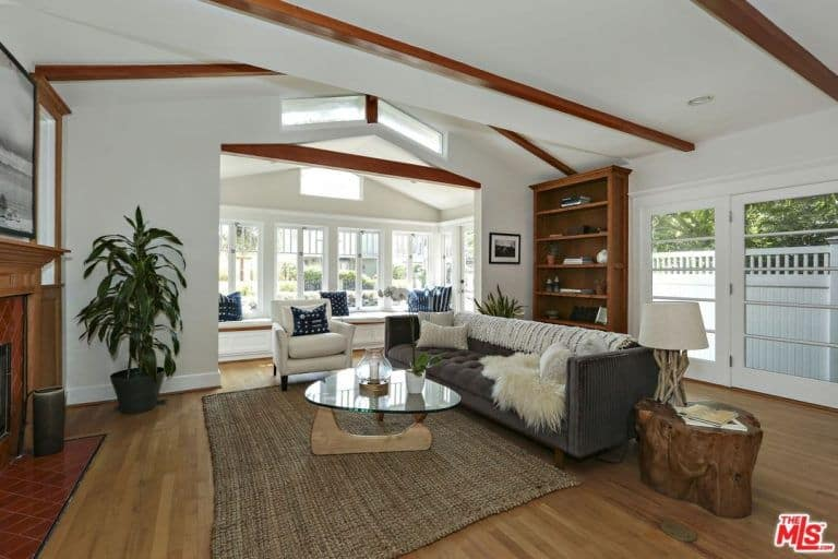 This living room has a comfortable dark gray sofa paired with a glass-top coffee table over the brown woven area rug. This setup faces a fireplace that has a wooden mantle that blends with the wooden exposed beams of the white ceiling.