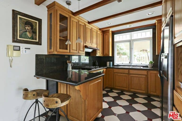 This is a small and compact kitchen that has no room for a kitchen island but has U-shaped peninsula that has a black countertop that matches with the checkered flooring. This is balanced by the wooden cabinetry that blends well with the beams of the white ceiling.