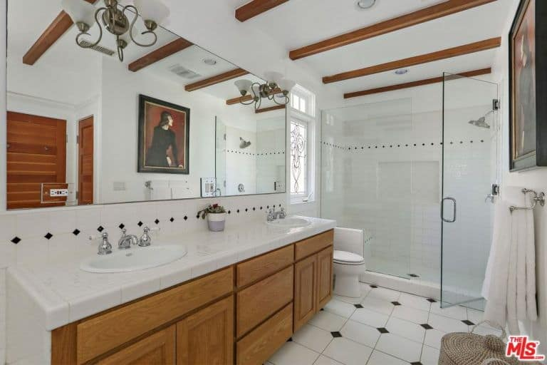 This brilliant primary bathroom has white walls and white flooring studded by small black diamond patterns on the flooring, backsplash and the walls of the glass-enclosed shower area. The small wooden beams of the ceiling and the wooden vanity serve to balance this.