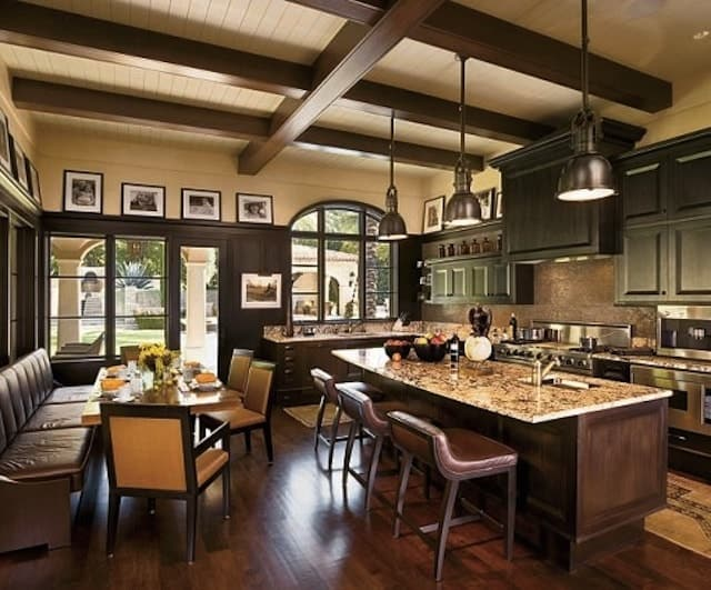 This large room houses both the kitchen and its dining area that has the same brown wooden hue to its cushioned bench as the kitchen island. These blend well with the hardwood flooring and the exposed beams that stand out against the beige ceiling and upper walls.