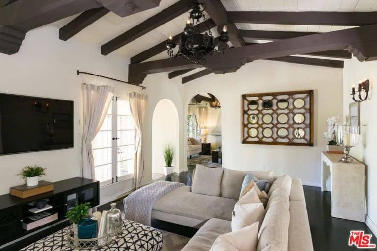 The dark hardwood flooring of this living room is dominated by the large gray L-shaped sectional sofa that faces a black TV with a black entertainment cabinet. This contrast is mirrored by the exposed wooden beams of the ceiling as well as the wrought iron chandelier.
