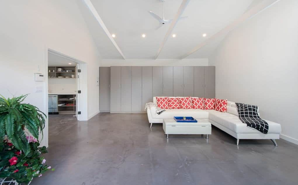The bright white ceiling of this spacious living room has exposed beams, recessed lights and a ceiling fan all in a white tone. This is mirrored by the large L-shaped sectional sofa and its cushioned coffee table that stands out against the Industrial-style gray concrete flooring.