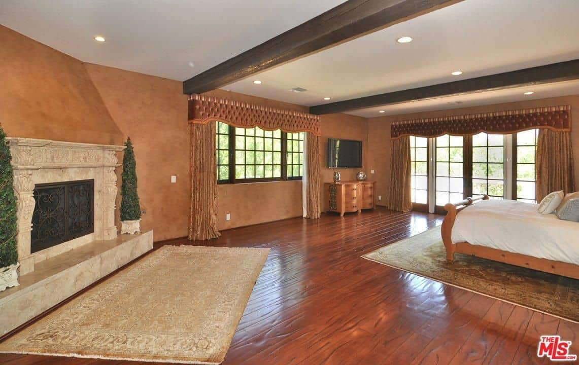 This is a spacious primary bedroom with chocolate brown walls that make the off white mantle of the fireplace stand out as well as the white ceiling that is contrasted by its large and thick dark wooden beams. This is paired with a wooden sleigh bed that matches the textured hardwood flooring.