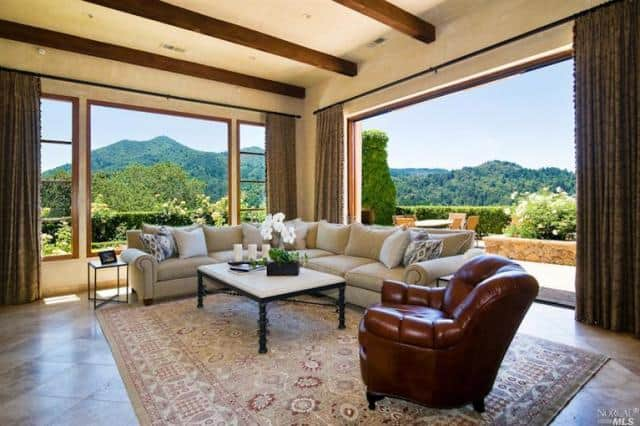 The large L-shaped sectional sofa of this living room is placed on a corner that is dominated by the large glass window on one side and a large open wall on the wall adjacent to it. These presents a beautiful scenery that goes well with the beige ceiling that is contrasted by the dark wooden beams.