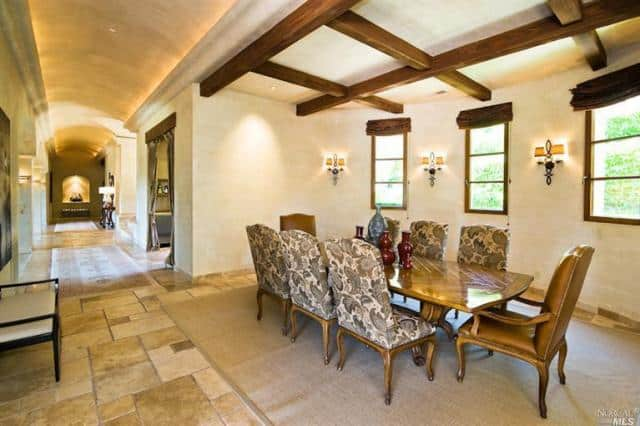The beige cove ceiling of this hallway transitions to a flat ceiling over the dining area. This is then adorned with a set of exposed wooden beams that form a checkered pattern. This complements the wooden dining table that is paired with patterned chairs.