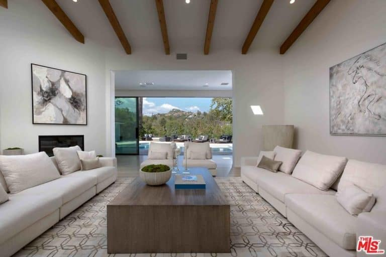This is a bright and charming living with a simple minimalist quality to its two cushioned beige sofas, the large simple wooden coffee table that stands out against the light hue of the patterned area rug. This is also true for the dark wooden exposed beams that stand out against the ceiling and walls.