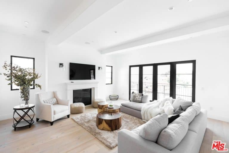 The white exposed wooden beams are almost indiscernible against the stark white ceiling that is further brightened by the tall glass windows on the side of the large light gray L-shaped sectional sofa that is paired with an impressive brass coffee table.