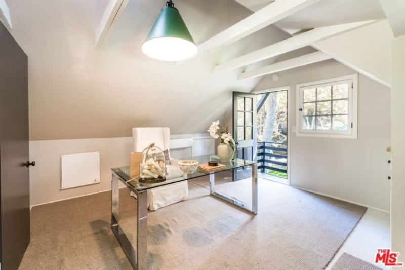 A gray area rug covers most of the white flooring of this simple and modern home office. This has a glass-top modern desk that goes pretty well with the light gray walls and light gray ceiling with exposed wooden beams and a large green dome pendant light.