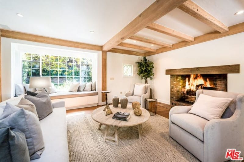 The light gray sofa set of this living room is augmented by the large fireplace on the beige wall with a wooden mantle that matches well with the wooden exposed beams of the ceiling as well as those supporting the walls as columns by the reading nook.