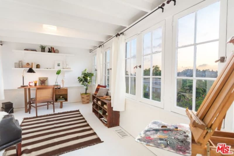 This is a bright and airy home office with a row of windows bringing in an abundance of natural lights to make the white elements shine on the floor, walls and ceiling with exposed beams. These make the brown and wooden elements stand out.