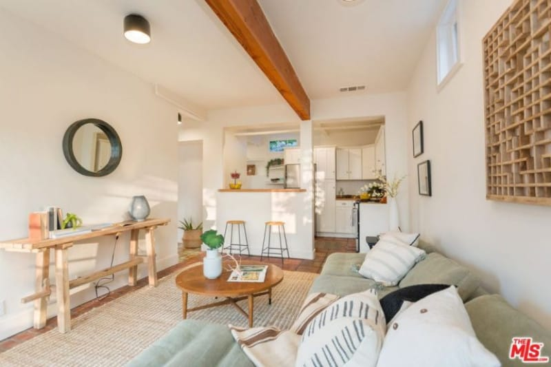 A single large exposed wooden beam is at the white ceiling that blends with the white walls. These walls are adorned with a wooden console table and a wooden artwork mounted above the L-shaped sofa in this living room that has terracotta flooring tiles mostly covered with a woven area rug.