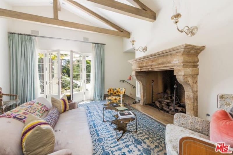 The triangular exposed wooden beams of the cathedral ceiling matches perfectly with the tone of the large mantle that surrounds the fireplace. This is contrasted by the blue patterned area rug by the large light gray cushioned sofa paired with floral armchairs.