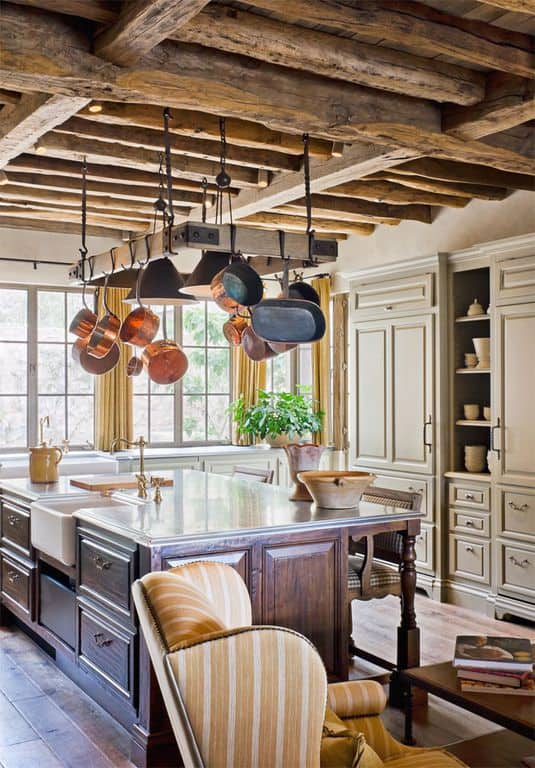 This bright kitchen has elegant and classy cabinets and drawers on its dark wooden kitchen and light gray kitchen cabinet on the wall. These are given a rustic contrast of a wooden ceiling that has rough and textured exposed wooden beams.