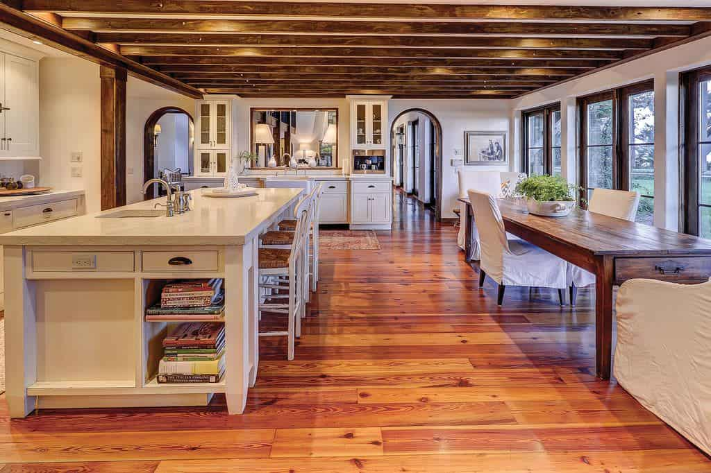 This large kitchen is dominated by the wooden elements of the exposed beams and the hardwood flooring that complements the beige shaker cabinetry of the island and peninsula. The wooden exposed beams of the ceiling are given emphasis with yellow recessed lights.