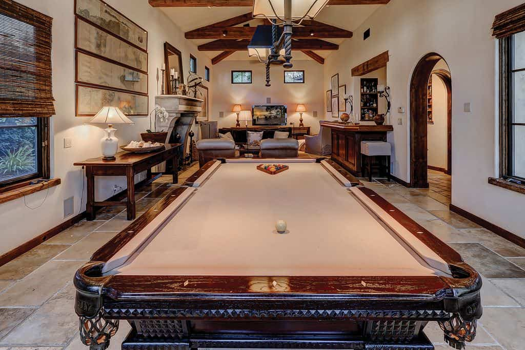 This is a view of the large great room that houses the living room on the far side and a game area next to it with a pool table in the middle under wrought iron pendant lights that hangs from the high cathedral ceiling with exposed wooden beams matching the other wooden elements of the room.