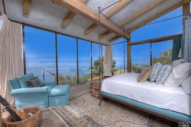 The thick wooden beams in this rustic bedroom is holding up the shed gray ceiling as well as the brilliant glass walls that showcase an amazing view. This matches with the light blue cushion of the platform bed as well as the cushioned armchair.