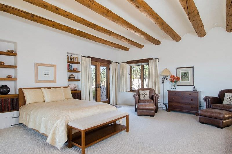 This primary bedroom has a white ceiling with a curved wave pattern with exposed wooden log beams embedded into it. This is mirrored by the embedded wooden shelves flanking the brown traditional bed that stands out against the white walls and the white carpeted flooring.