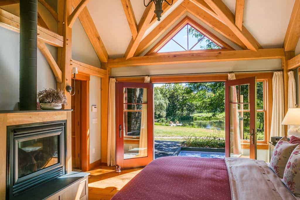 The wooden beams of the arched ceiling extends to the walls of this charming bedroom. This also extends to the frames of the glass doors, windows and even the modern fireplace that is enclosed with glass by the foot of the cottage bed.