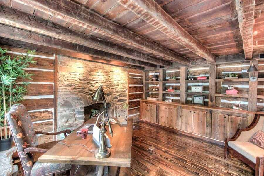 This is an elegant home office has a fireplace on the side housed within a large stone panel with a textured rustic finish. This is complemented by the various wooden elements surrounding it like the exposed wooden beams of the ceiling, wooden walls, hardwood flooring and bookshelves.