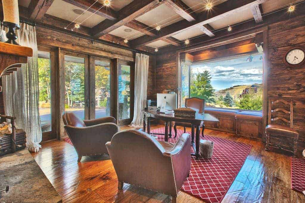 The dark wooden thick beams of the ceiling form a checkered pattern that is mirrored by the red patterned area rug that tops the sleek and shiny hardwood flooring brightened by the natural lights of the large glass window and the glass doors.
