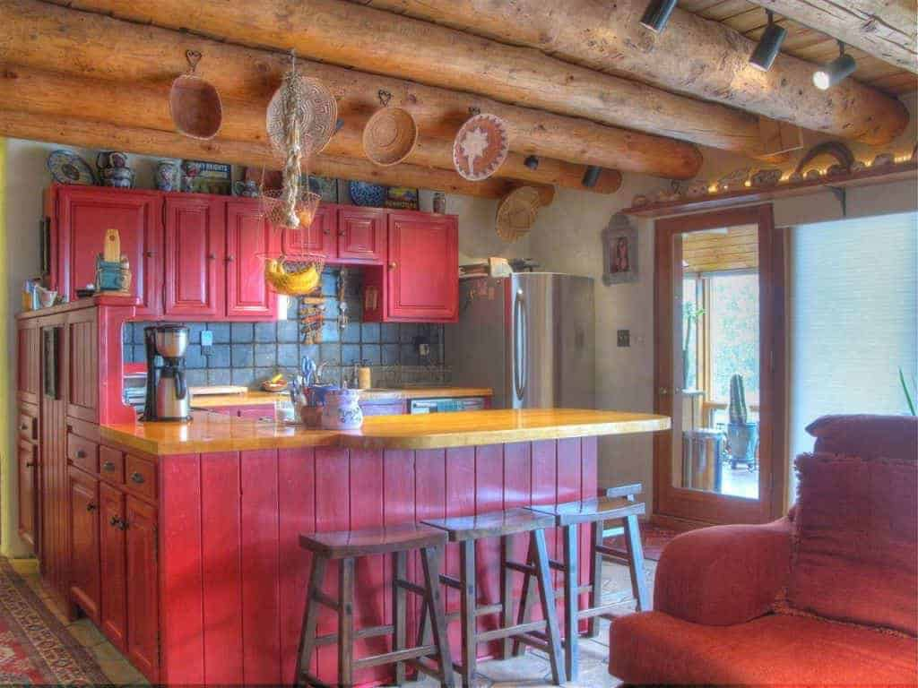 The exposed wooden log beams of the ceiling are adorned with decorative earthy plates. This serves as a nice background for the small U-shaped kitchen peninsula with a red wooden tone and a countertop that matches the wooden ceiling.