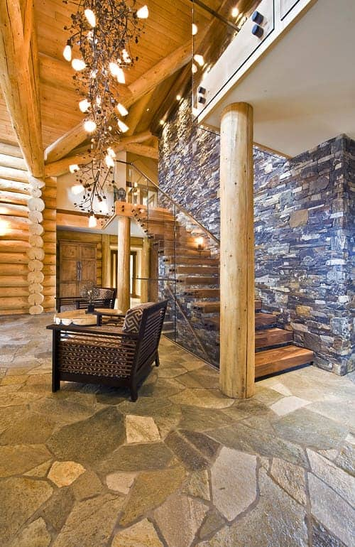 The large log columns of this charming foyer are a match for the loge beams of the walls and the ceiling that hangs a large decorative string of pendant lights over the coffee table flanked by armchairs. These two stand out against the gray tones of the mosaic flooring.