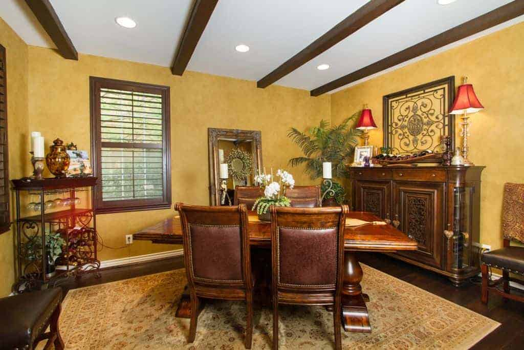 The beige walls and the patterned area rug has the same amber tone to it like an earthy yellow. This does well with the addition of the dark wooden elements of the wooden dining set, cabinets, window frames and the exposed wooden beams of the white ceiling.