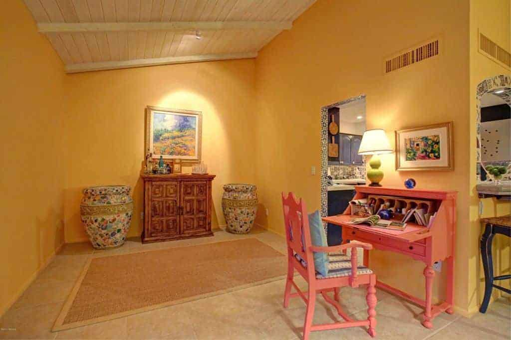 This is a small hall that leads to the kitchen through a walkway beside the pink furniture of the study area. This stands out against the delightful yellow walls. This area is also adorned with a small wooden cabinet flanked by decorative jars and topped with a painting.