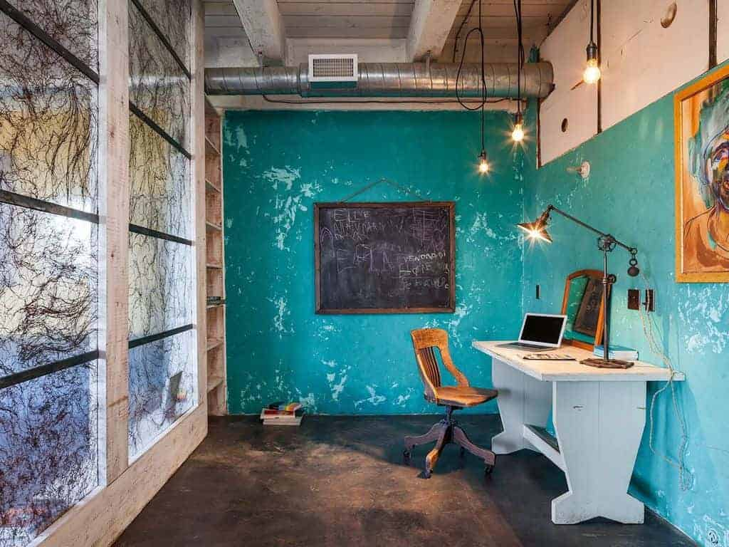 This is a simple study area with an Industrial-style vibe to its exposed wooden beams, exposed air vents and the distressed bright green walls that makes the off-white wooden desk stand out especially against the dark flooring that matches the chalk board.