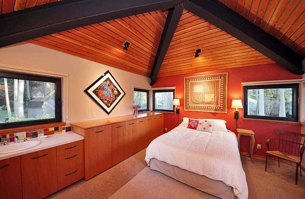 This is a gorgeous primary bedroom with an orange tone to its walls, wooden shiplap ceiling that has contrasting black beams as well as the row of dressers on the side leading to a vanity area with its own white porcelain sink that matches the countertop.