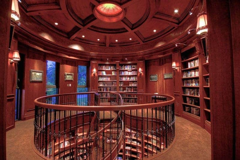The circular shape of the library is followed by its elegant wooden ceiling with exposed beams of the same redwood hue as the rest of the library. This makes the books stand out as well as the various colorful painting that are illuminated by the wall lamps.