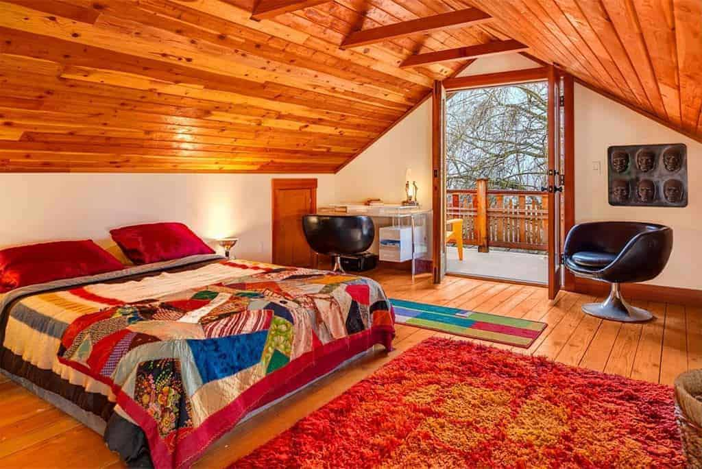 This comfortable primary bedroom has a low wooden cathedral ceiling with beams on its upper sections parallel to the frame of the glass doors that lead to a balcony. This also brings in natural lighting that brightens the hardwood flooring topped with an orange area rug matching the colorful tones of the bed.
