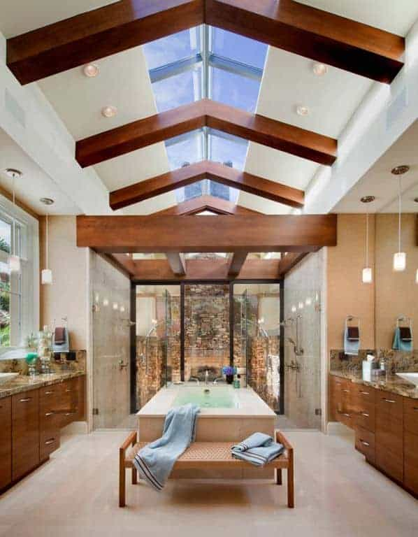 The middle part of the cathedral ceiling in this primary bathroom is lined with a row of sky lights supported by thick wooden beams. This brings in an abundance of natural lights to the bathtub beside the glass-enclosed shower area large enough for two.