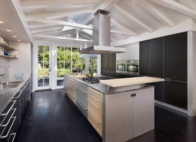 The beauty of this modern kitchen is seen on its elegant contrasting of the black cabinetry, flooring and the stove top. These are counterbalanced by the white ceiling with exposed wooden beams as well as support for the stainless steel bent hood of the vent.