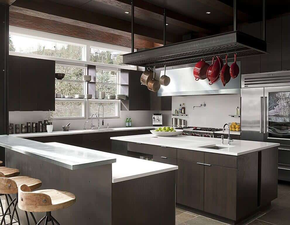 This is a large kitchen with enough floor space for two kitchen islands with the same bright white countertop that matches the white backsplash of the L-shaped peninsula contrasted by the dark wooden beams of the ceiling that supports a pot rack in the middle.