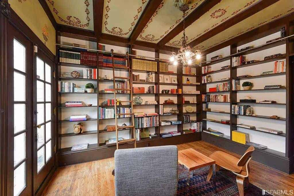 This simple library has two adjacent walls dominated by large built-in bookshelves that reach all the way to the beige ceiling where the dark wooden shelves fuse with the exposed wooden beams of the same tone. This is complemented by the chandelier.
